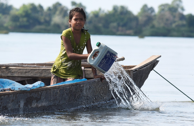 A child pours water from her boat